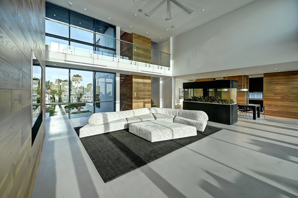 Modern home with walkways, horizontal fence, planters patio, porch, deck, large patio, porch, deck, decking patio, porch, deck, hardscapes, grass, shrubs, trees, front yard, boulders, sectional, bed, night stands, wall lighting, ceiling lighting, engineered quartz counter, ceramic tile floor, concrete floor, and undermount sink. living room Photo 19 of Atlantic Beach Modern