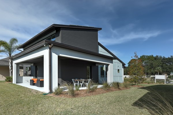 Modern home with dresser, bed, engineered quartz counter, chair, ceramic tile floor, undermount sink, alcove tub, ceiling lighting, carpet floor, ceramic tile wall, two piece toilet, front yard, trees, shrubs, grass, walkways, and outdoor. rear and side porch Photo 5 of Cedarbrook Net Zero Modern