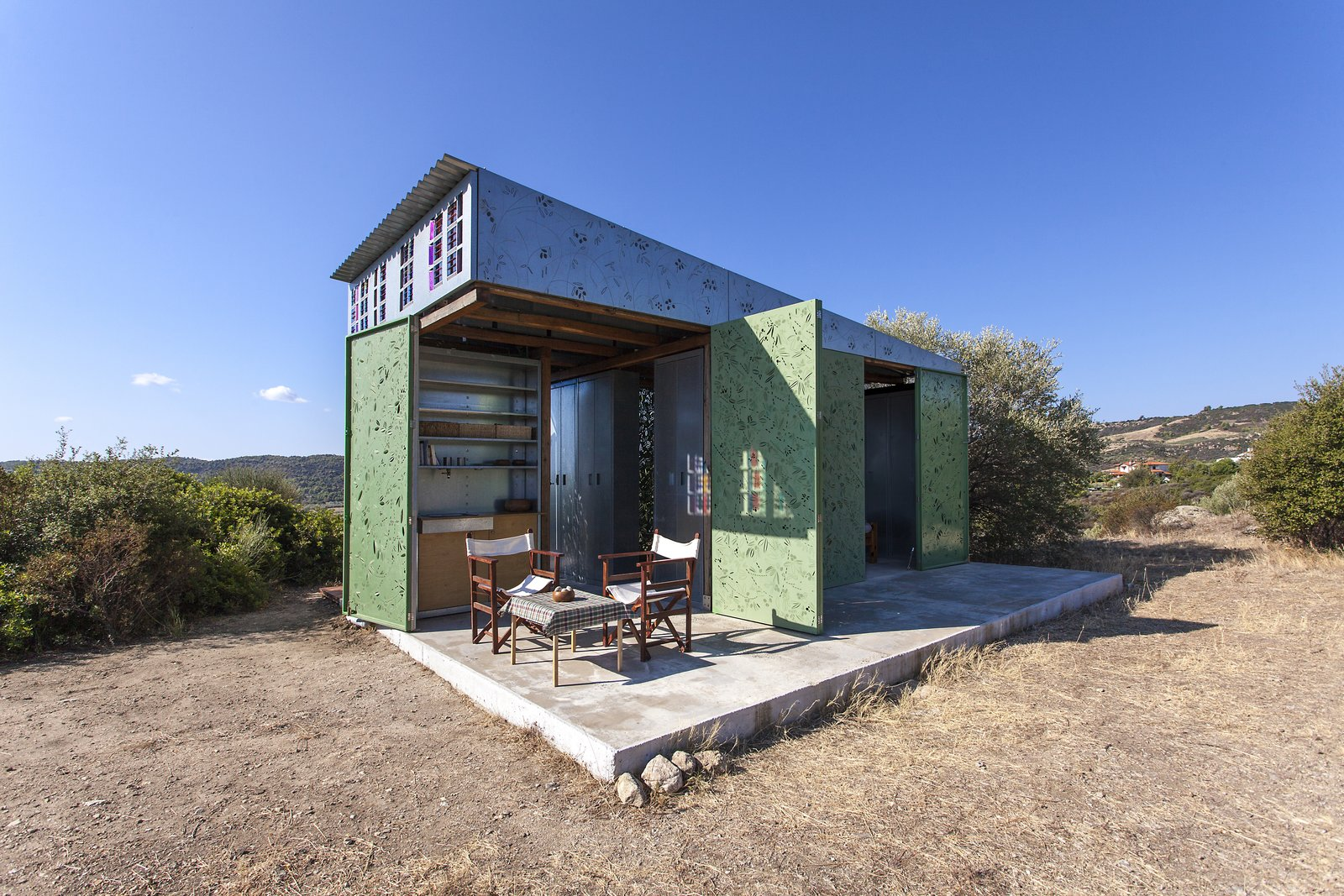 The Olive Tree House in Sithonia, Halkidiki, Greece Tagged: Wood Counter, Metal Cabinet, Concrete Floor, Wood Cabinet, Chair, Coffee Tables, Table, Desert, Trees, Shrubs, Small Patio, Porch, Deck, and Doors.  The Olive Tree House by Eva Sopeoglou