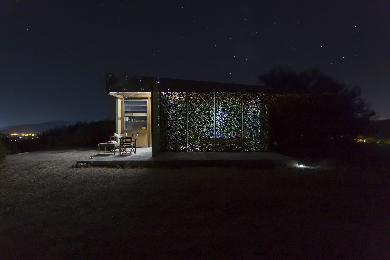 Night view Tagged: Wood Counter, Wood Cabinet, Concrete Floor, Metal Cabinet, Chair, Coffee Tables, Table, Trees, Shrubs, Small Patio, Porch, Deck, Exterior, Metal, Folding Door Type, Metal Counter, Living Space, Bed, Accent Lighting, Garden, Desert, and Hardscapes.  The Olive Tree House by Eva Sopeoglou