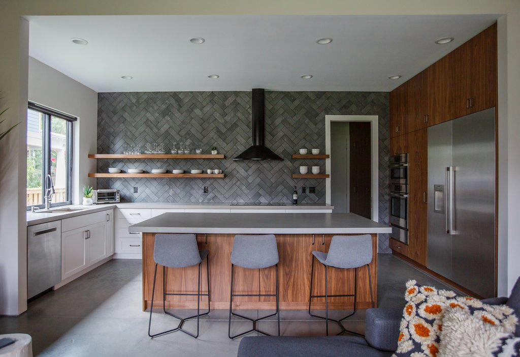 Kitchen Tagged: Kitchen, Engineered Quartz Counter, White Cabinet, Concrete Floor, Ceramic Tile Backsplashe, Ceiling Lighting, Wood Cabinet, Refrigerator, Wall Oven, Cooktops, Range Hood, and Undermount Sink. HoF by Nicholas Renard
