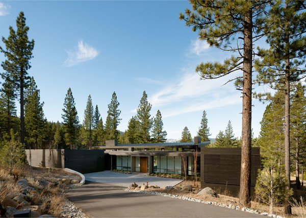 Modern home with outdoor, front yard, trees, shrubs, and boulders. Entry Photo 2 of Martis Camp Residence 1