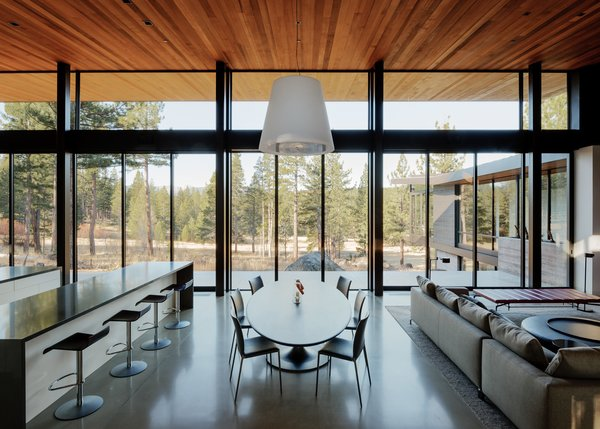 Modern home with dining room, pendant lighting, concrete floor, table, chair, and stools. Dining Room Photo 4 of Martis Camp Residence 1