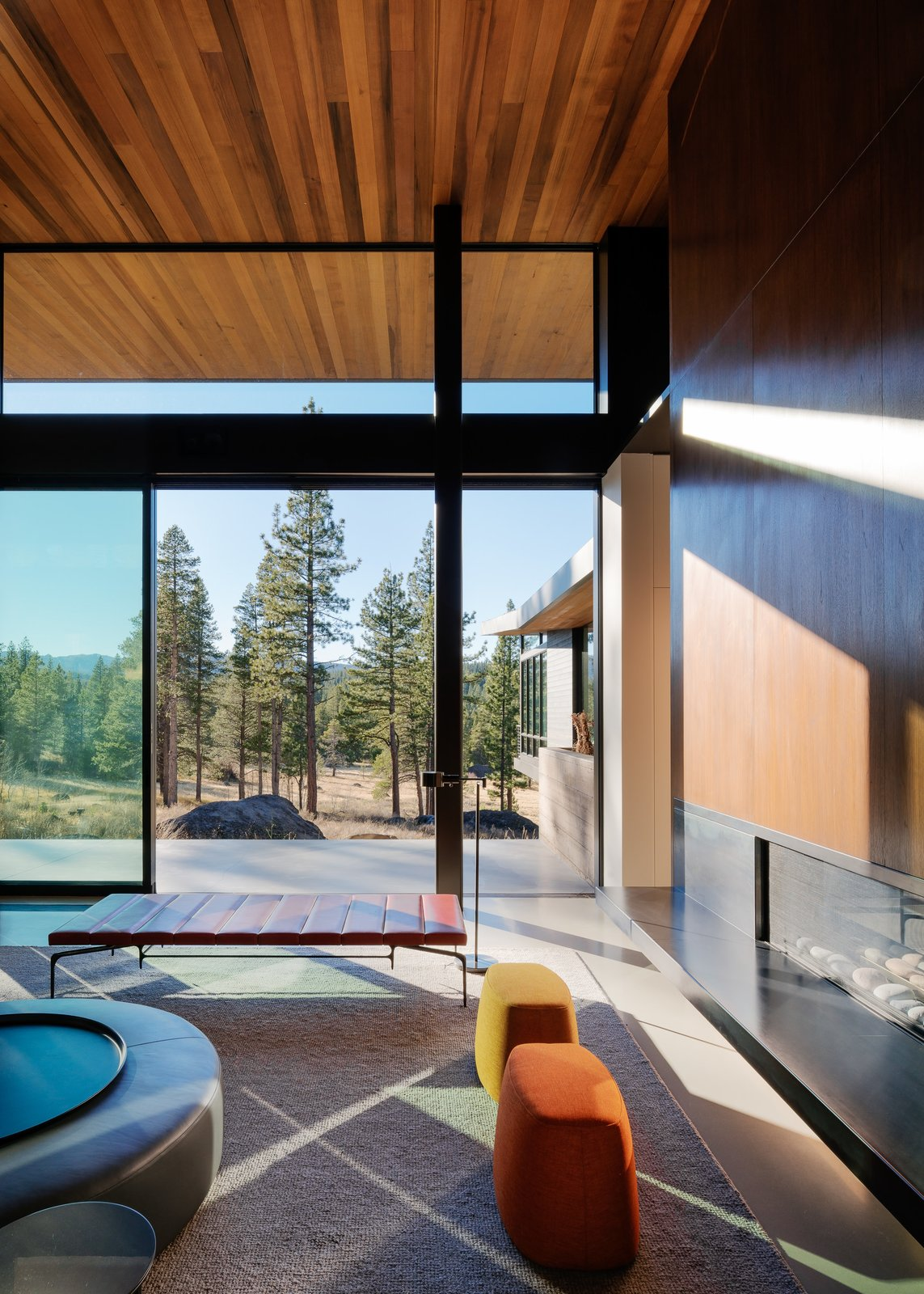 Living Room Tagged: Living Room, Ottomans, Ribbon Fireplace, Bench, Concrete Floor, and Gas Burning Fireplace.  Martis Camp Residence 1 by John Maniscalco Architecture