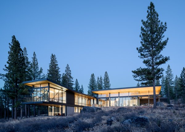Modern home with outdoor, back yard, boulders, trees, shrubs, flowers, and large patio, porch, deck. Rear Facade Photo  of Martis Camp Residence 1