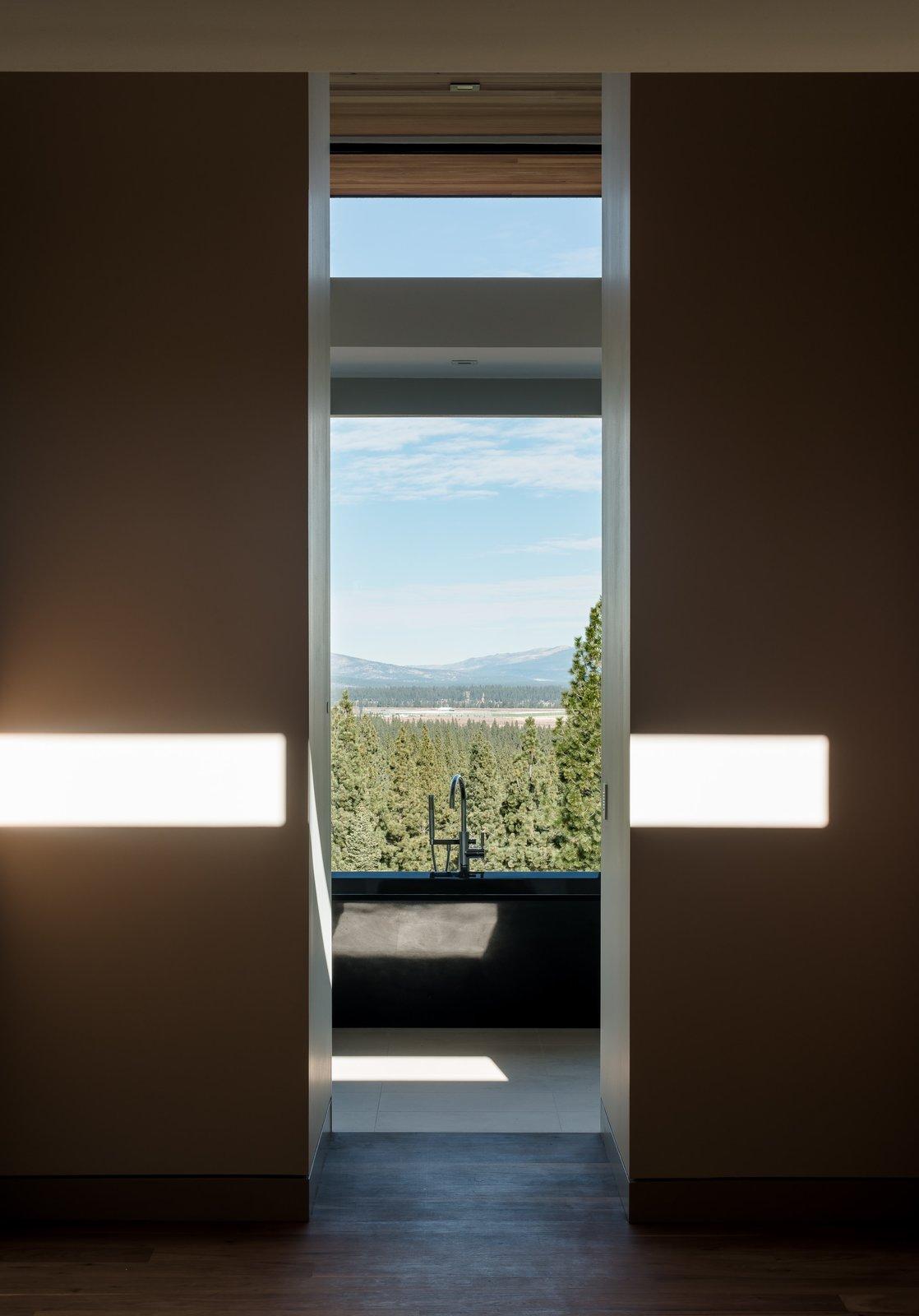 Tagged: Bath Room, Medium Hardwood Floor, Porcelain Tile Floor, and Freestanding Tub.  Martis Camp Residence 2 by John Maniscalco Architecture