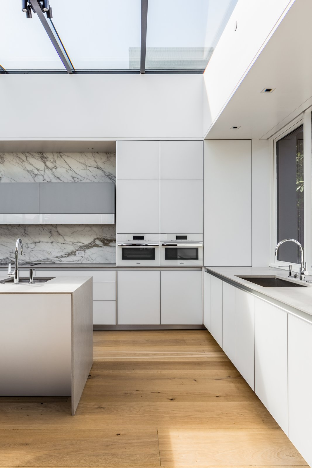 Tagged: Kitchen, Concrete Counter, White Cabinet, Light Hardwood Floor, Marble Backsplashe, Ceiling Lighting, Recessed Lighting, Wall Oven, Microwave, and Undermount Sink.  Spruce by John Maniscalco Architecture