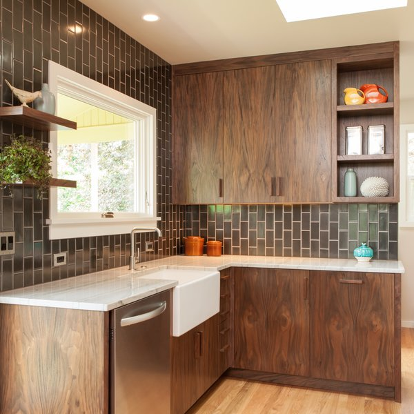 Modern home with kitchen, marble counter, wood cabinet, and ceramic tile backsplashe. Walnut + gunmetal: Our goal was to be bold but not cold. Handmade tile adds a humane touch. Richly textured walnut cabinetry and pulls add warmth. Photo 2 of Holly + Magda