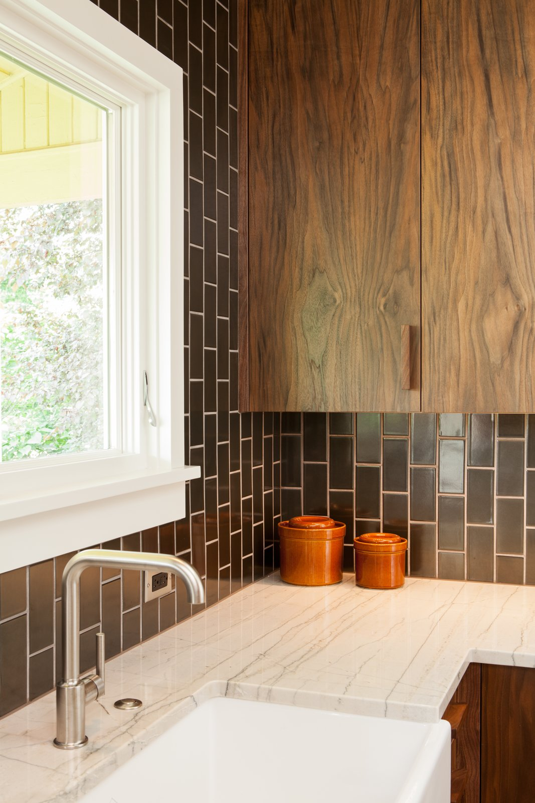 Walnut + gunmetal: Our goal was to be bold but not cold. Handmade tile adds a humane touch. Richly textured walnut cabinetry and pulls add warmth. Tagged: Kitchen, Granite Counter, Ceramic Tile Backsplashe, and Wood Cabinet.  Holly + Magda by Howells Architecture + Design