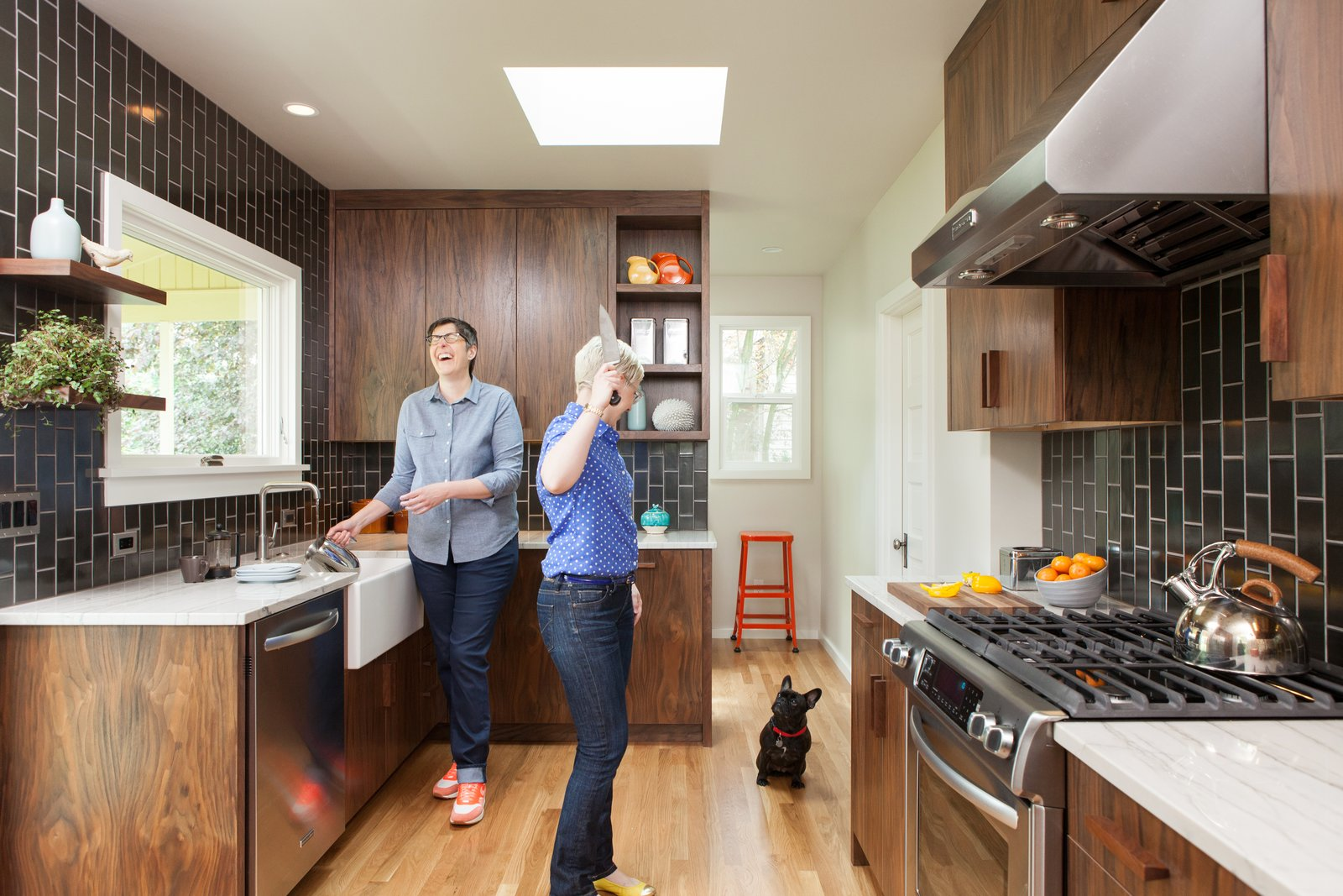 Tall, dark, and handsome: We aimed for midcentury-inspired design, while respecting the long lines and existing layout of this 1909 home. Tagged: Kitchen, Quartzite Counter, Wood Cabinet, Medium Hardwood Floor, Ceramic Tile Backsplashe, Ceiling Lighting, Range, and Drop In Sink.  Holly + Magda by Howells Architecture + Design
