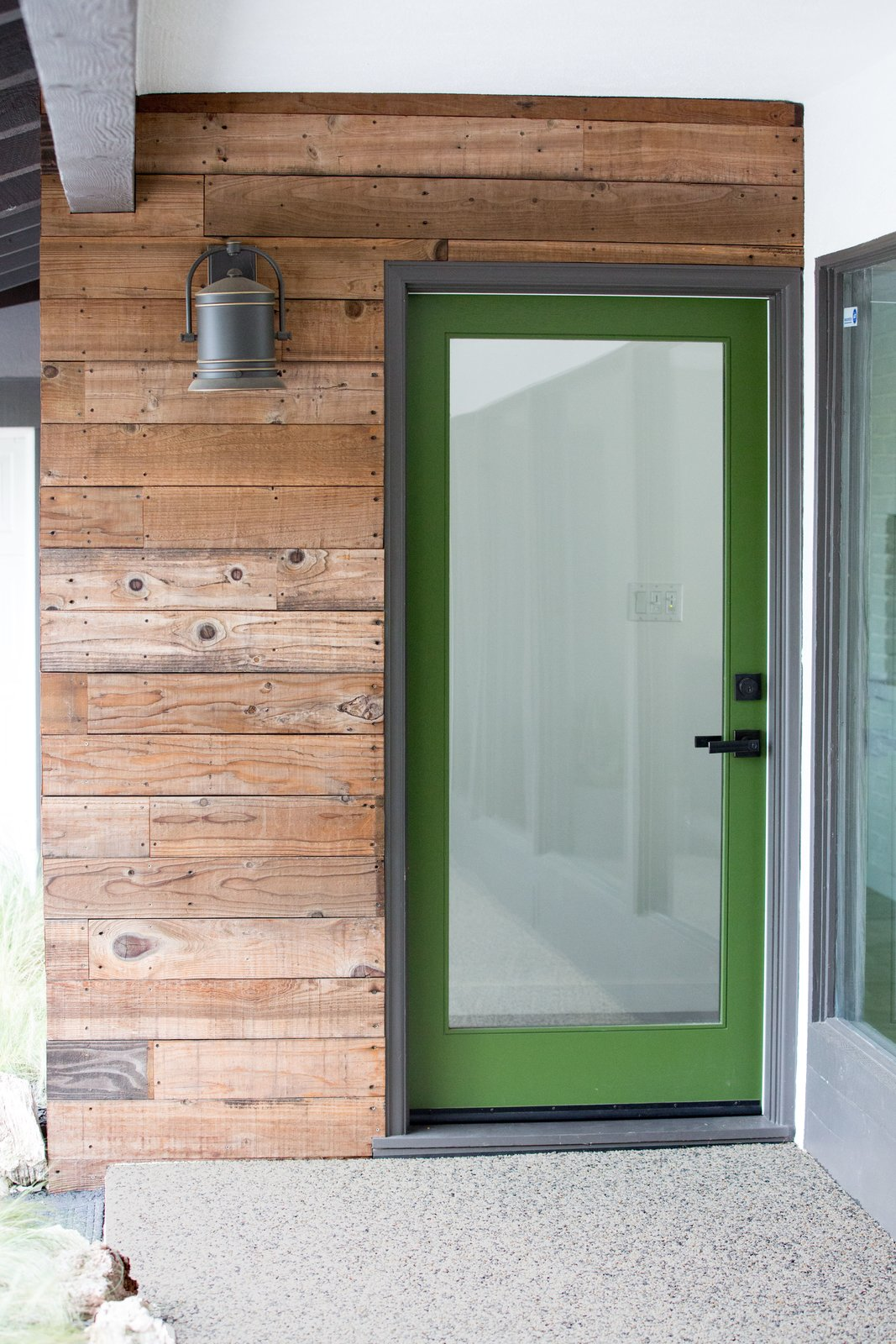 A grass green front door draws from the verdant foliage blanketing the 38,000 sq. ft. hillside property. Its earthy tone complements the rich warmth of reclaimed fence wood that finds new life as siding. Tagged: Front Yard, Boulders, Small, Hardscapes, Walkways, Stone, Doors, Exterior, Wood, and Swing.  Best Doors Walkways Small Photos from Diablo Ranch