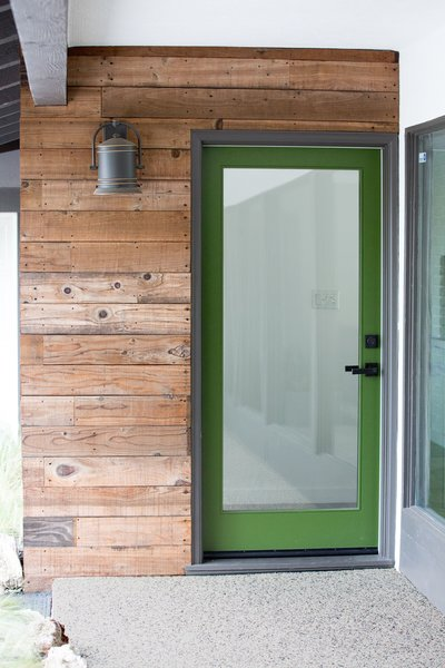 A grass green front door draws from the verdant foliage blanketing the 38,000 sq. ft. hillside property. Its earthy tone complements the rich warmth of reclaimed fence wood that finds new life as siding.