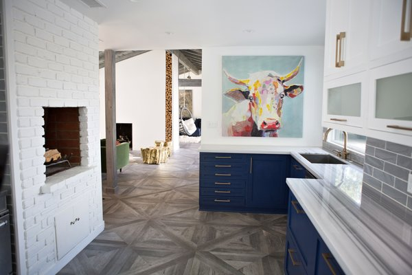 Modern home with kitchen, colorful cabinet, subway tile backsplashe, marble counter, porcelain tile floor, porcelain tile backsplashe, recessed lighting, and undermount sink. To keep this farmhouse modern, familiar items in new colors make the design exciting.  Navy cabinets, gold tree trunks, a technicolor cow painting, and pinstripe marble counters add surprise and a touch of whimsy. Photo 14 of Diablo Ranch