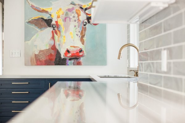 Modern home with kitchen, marble counter, colorful cabinet, subway tile backsplashe, and porcelain tile backsplashe. Matte gold hardware and fixtures add a touch of luxury to balance out the colorful farmhouse art, like this oversized cow portrait. Photo 15 of Diablo Ranch