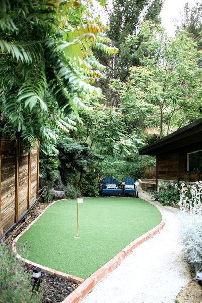 Modern home with outdoor, front yard, trees, flowers, shrubs, grass, hardscapes, raised planters, walkways, gardens, horizontal fence, wood fence, and landscape lighting. Instead of a traditional front yard, a playful putting green welcomes guests at the entry gate. Photo 6 of Diablo Ranch