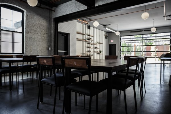 Modern home with chair, ceiling lighting, concrete floor, and dining room. steel supports were conserved and painted and original brick walls were preserved and white-washed Photo 3 of The Lytle House