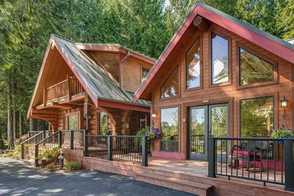 Modern home with outdoor, small patio, porch, deck, wood patio, porch, deck, gardens, trees, front yard, shrubs, and raised planters. www.SnohomishEquestrianLodge.com Photo 2 of Snohomish Equestrian Lodge