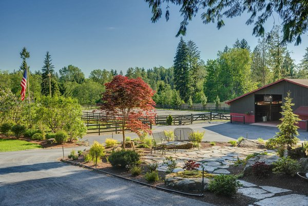 Modern home with outdoor, shrubs, grass, flowers, trees, gardens, hardscapes, and walkways. www.SnohomishEquestrianLodge.com Photo 4 of Snohomish Equestrian Lodge