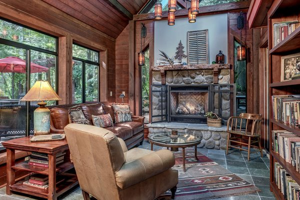 Modern home with living room, chair, recliner, coffee tables, sofa, ceiling lighting, wood burning fireplace, and bookcase. www.SnohomishEquestrianLodge.com Photo 6 of Snohomish Equestrian Lodge