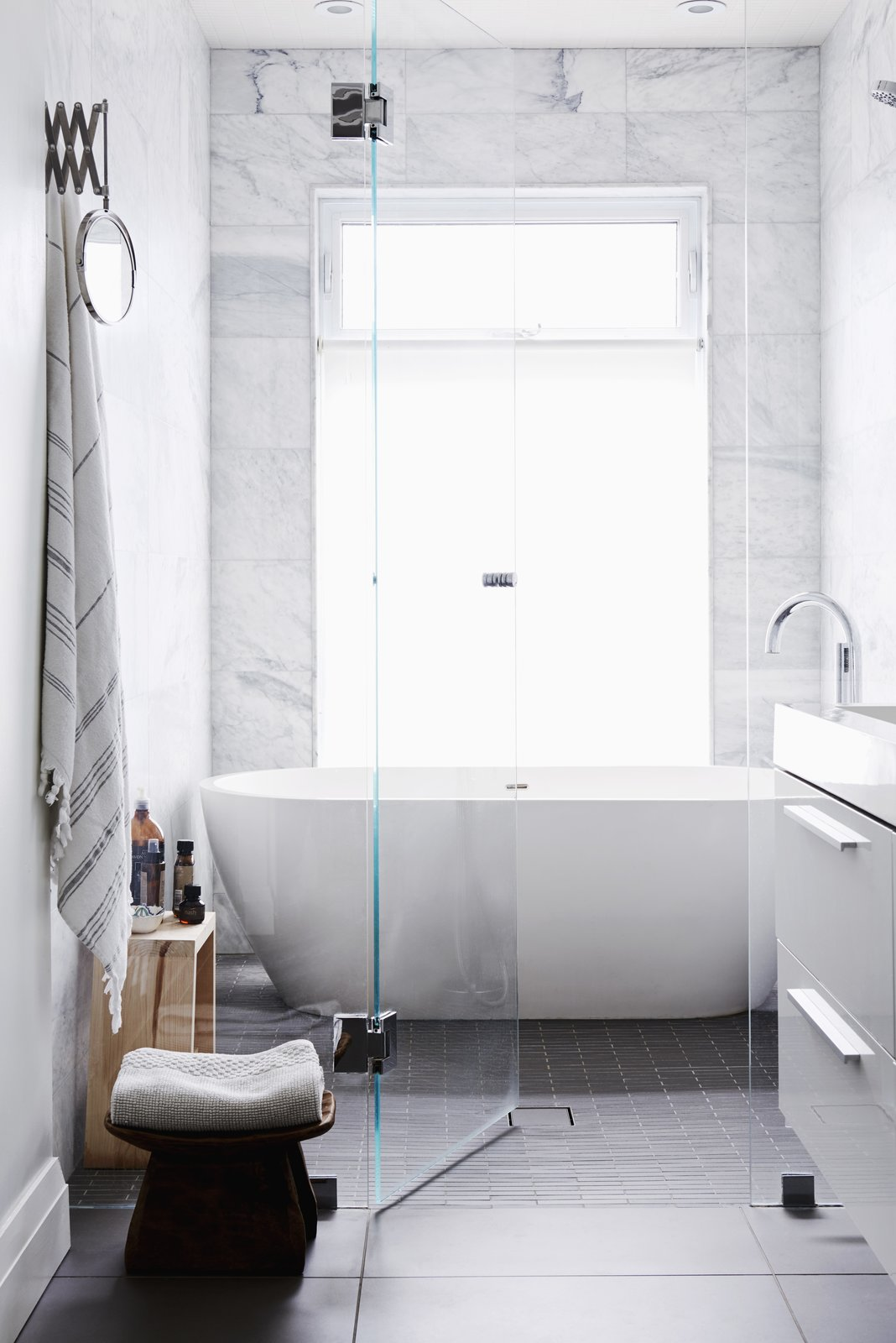 A glass wall divides the wet room from the vanity area. The wet room has a large soaker tub and rain head and is tiled in Carrara marble. The full height window maximizes natural light and allows for a visual link to the outdoors. A neutral palette and clean materials convey a sense of simplicity and calm, perfect for relaxing in the tub.   Tagged: Bath Room, Freestanding Tub, Porcelain Tile Floor, Enclosed Shower, Recessed Lighting, Wall Lighting, Marble Wall, and One Piece Toilet.  Best Photos from Family Bathroom Renovation