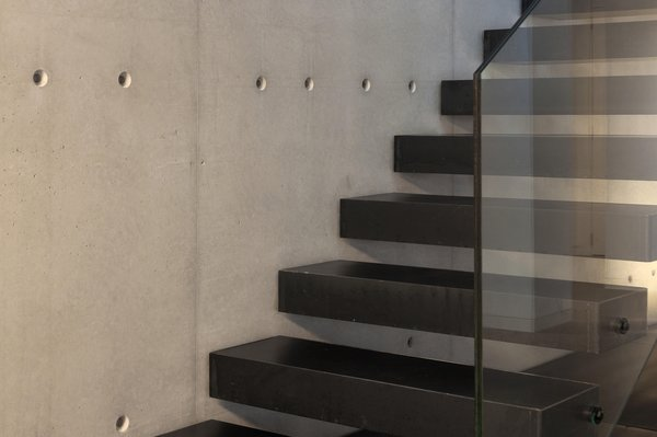 Modern home with staircase, metal tread, and glass railing. Photo 12 of Casa Forment