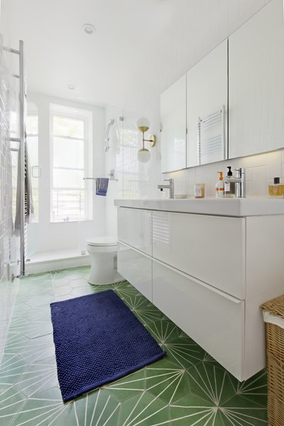 Modern home with bath room, marble counter, enclosed shower, drop in sink, full shower, subway tile wall, wall lighting, one piece toilet, and ceramic tile floor. Photo 5 of Creative Townhouse kitchen and bath (Sweeten project)