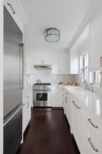 Modern home with kitchen, dark hardwood floor, refrigerator, drop in sink, wall oven, and white cabinet. Photo 5 of AN ART-FILLED APARTMENT RENOVATION 40 YEARS IN THE MAKING!