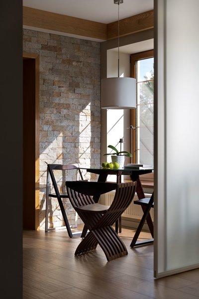 Modern home with kitchen, stone tile backsplashe, medium hardwood floor, pendant lighting, and wood cabinet. Photo  of House Lightray
