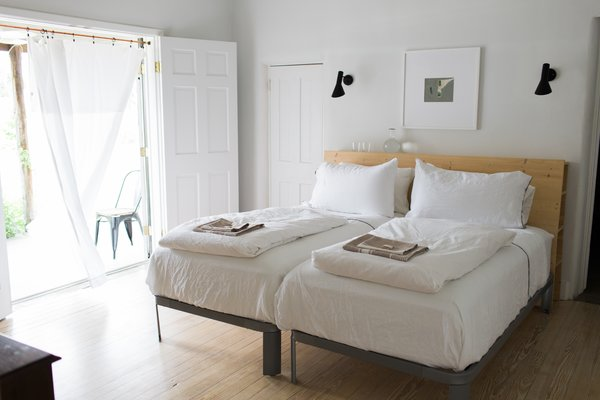 Modern home with bedroom, bed, wall lighting, and light hardwood floor. high-country breezes in the master bedroom; French doors open to ranch land views Photo  of PILGRIM HOUSE