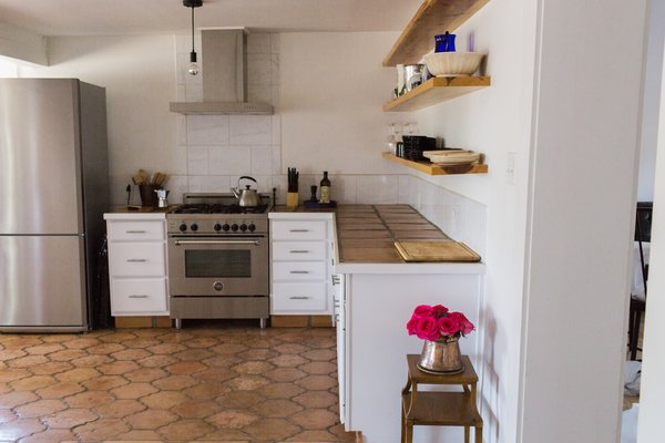 Modern home with kitchen, tile counter, white cabinet, pendant lighting, ceramic tile floor, range, and ceramic tile backsplashe. Bertazzoni stove, ranch shelves, mid-century side table, Daltile Florentine Carrara porcelain backsplash Photo 7 of PILGRIM HOUSE