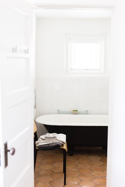 Modern home with bath room, freestanding tub, ceramic tile floor, and porcelain tile wall. Footed tub, the base of which is painted Railings by Farrow & Ball; Smedbo Air towel hooks in foreground Photo 14 of PILGRIM HOUSE