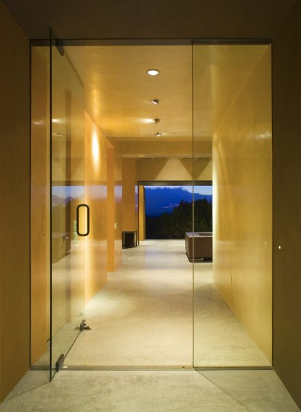 Modern home with living room, ceiling lighting, and concrete floor. The entry to the home includes a grand glass entrance with a stunning view of the Jemez Mountains. Photo 12 of Santa Fe Contemporary