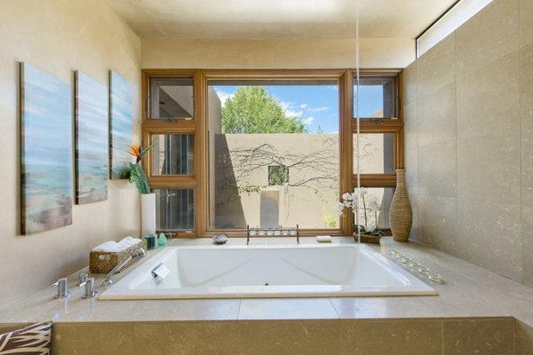 Modern home with bath room, stone counter, whirlpool tub, concrete floor, open shower, floor lighting, and stone tile wall. The master bath a spa retreat include a jetted oversized tub and the ceiling faucet which fill the bathtub. Photo 5 of Santa Fe Contemporary