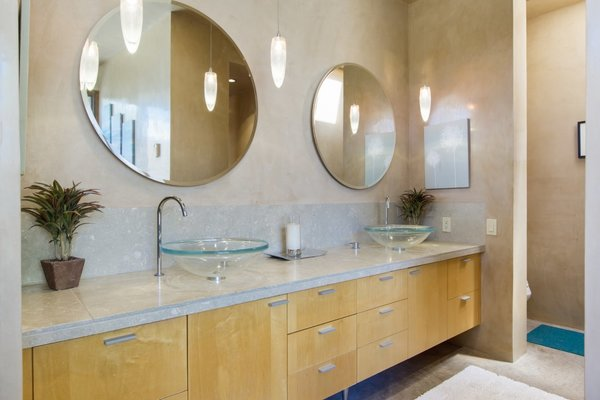 Modern home with bath room, vessel sink, concrete floor, pendant lighting, stone counter, and stone tile wall. The neutral master bath includes double glass vessel sinks, custom maple cabinetry and oversized limestone tiles. Photo 9 of Santa Fe Contemporary