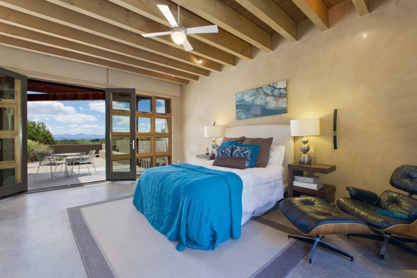 Modern home with bedroom, bed, night stands, chair, ceiling lighting, recessed lighting, and concrete floor. The oversized master bedroom includes a private courtyard and impressive Jemez Mountain and sunset views. Photo 7 of Santa Fe Contemporary