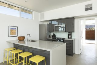 Bright, yellow stools accent a sleek kitchen in the main home.