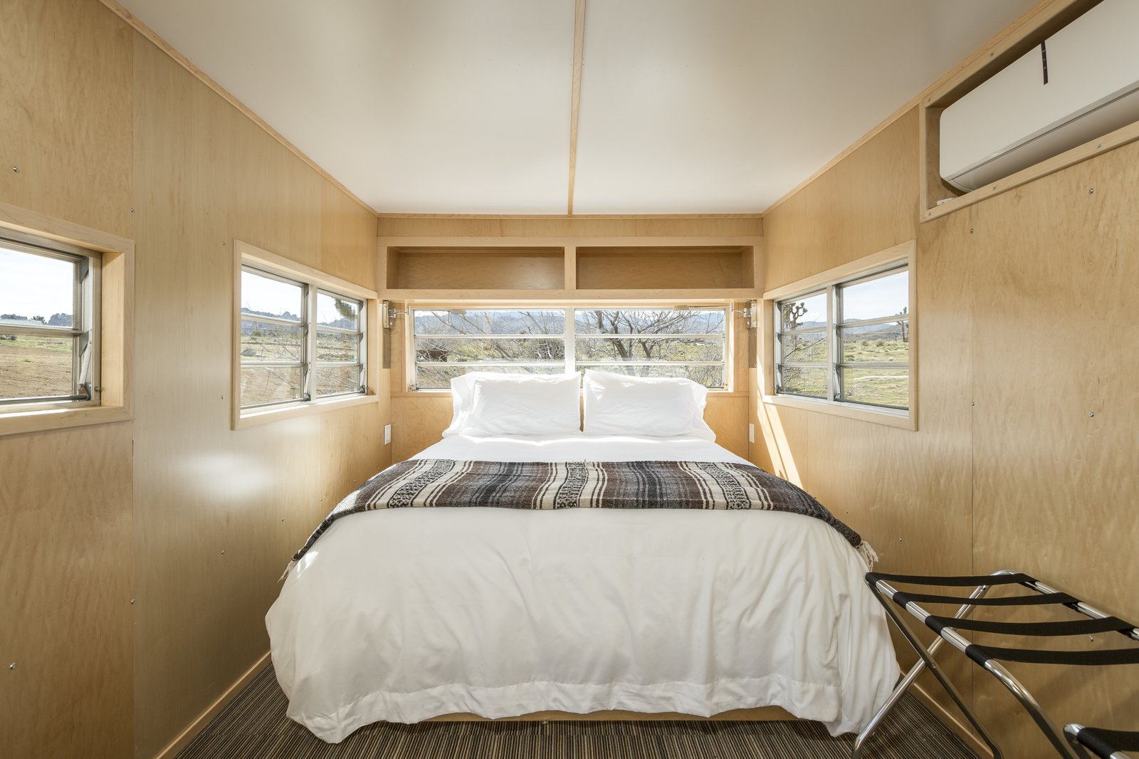 Interior of trailer.  The Rambler is now a clean, sleek retreat. Tagged: Bedroom, Bed, Wall Lighting, and Carpet Floor.  Photo 9 of 10 in This Modern Homestead With a Vintage Trailer Offers Adventure in California's High Desert