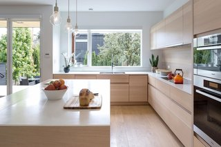 Custom Millwork and Bright Interiors Star in an Elegant Vancouver Home - Photo 3 of 9 - An alternate view of the kitchen shows custom millwork and a continuous wood backsplash, creating an effortlessly seamless connection.