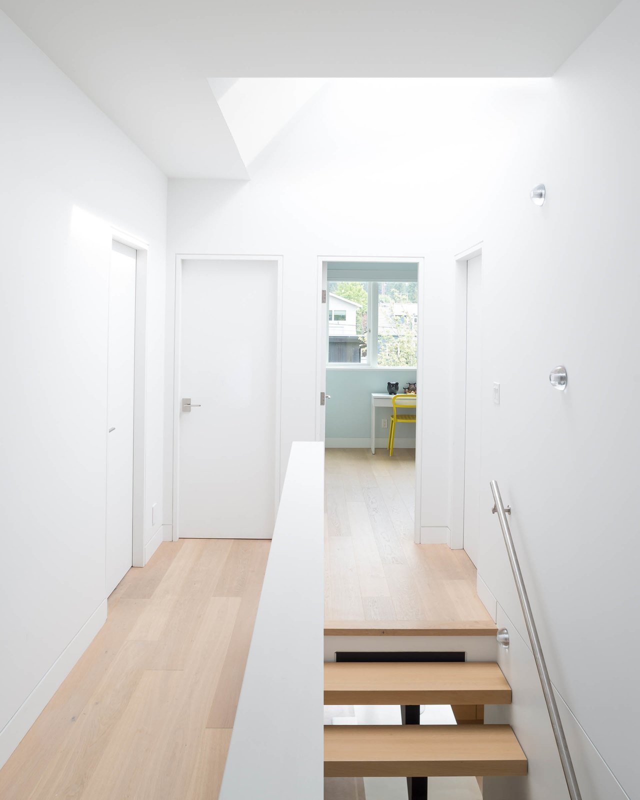 A projecting skylight offers an additional source of daylight from above, allowing light to pass down to all three floors below.