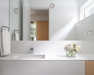 The bathroom palette blends seamlessly into the whole floor plan with white oak accents and decorative lighting.