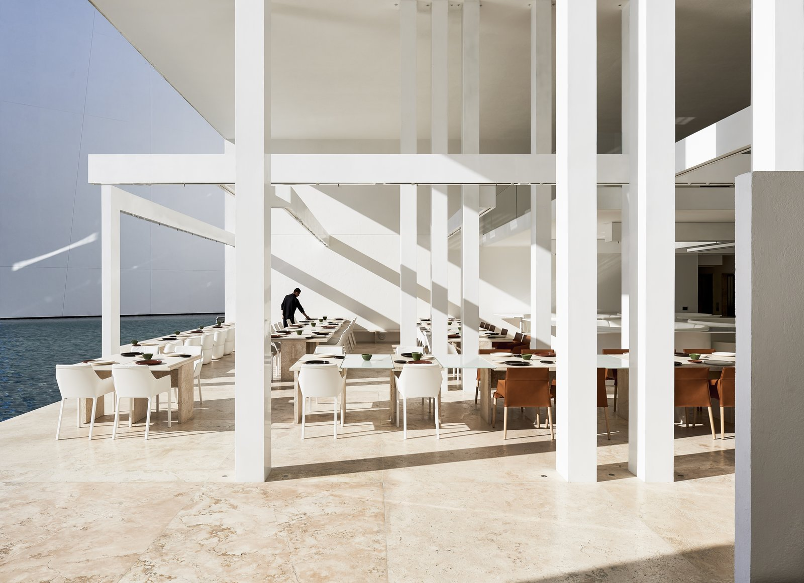 With white travertine floors and muted, modern furnishings by Poliform, this restaurant at the resort is all about the view of the ocean and the sensoral connectivity to it. Tagged: Desert, Large Patio, Porch, Deck, Dining Room, Travertine Floor, Chair, and Table.  Photo 2 of 12 in An Exquisite Beach Resort on Baja California Sur Lies Where the Water Meets the Horizon