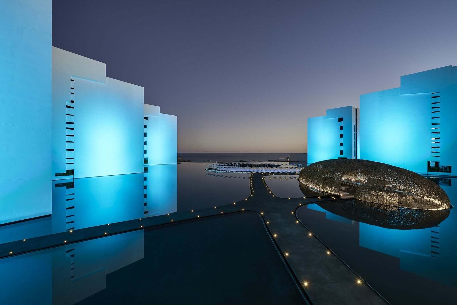 At night, the whole exterior is lit to shades of blue and purple. Tagged: Outdoor, Walkways, Large Pool, and Landscape Lighting. An Exquisite Beach Resort on Baja California Sur Lies Where the Water Meets the Horizon - Photo 11 of 12