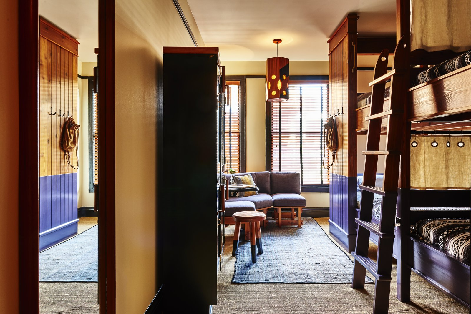 The shared rooms, the most affordable and popular option, are inventive in decor with bunk beds, draperies, and accents of purple. Tagged: Bedroom, Wardrobe, Pendant Lighting, Bed, Rug Floor, Ceiling Lighting, Storage, and Bunks. A 1920s Office Building Is Revamped as a Craftsman-Inspired Hotel in Los Angeles - Photo 9 of 10