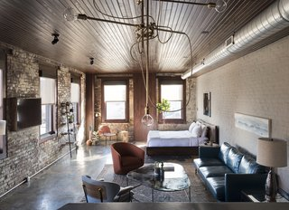 History and Modernity Meet in This Industrial Hotel and Restaurant in Philadelphia - Photo 2 of 11 - Room 1, located on the second floor,  blends industrial detailing with exposed brick walls, polished concrete floors, rich textile finishes, and a custom walnut bed.