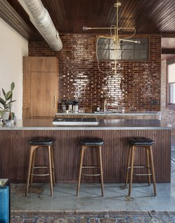 History and Modernity Meet in This Industrial Hotel and Restaurant in Philadelphia - Photo 3 of 11 - In the kitchenette area, seamless walnut cabinets, poured concrete countertops, and glazed brick tiles introduce minimalistic, modern elements.