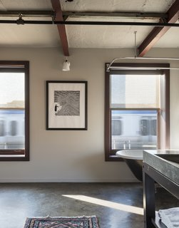 History and Modernity Meet in This Industrial Hotel and Restaurant in Philadelphia - Photo 7 of 11 - An original clawfoot tub rests below the windows, looking out to the train tracks beyond. A poured concrete sink with steel legs introduces modern elements that blend with the historic character.