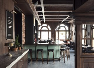 History and Modernity Meet in This Industrial Hotel and Restaurant in Philadelphia - Photo 8 of 11 - A quote bar hangs on the wall upon entry into the bar. Walnut wood tones and black furnishings are accented by the green pastel bar.