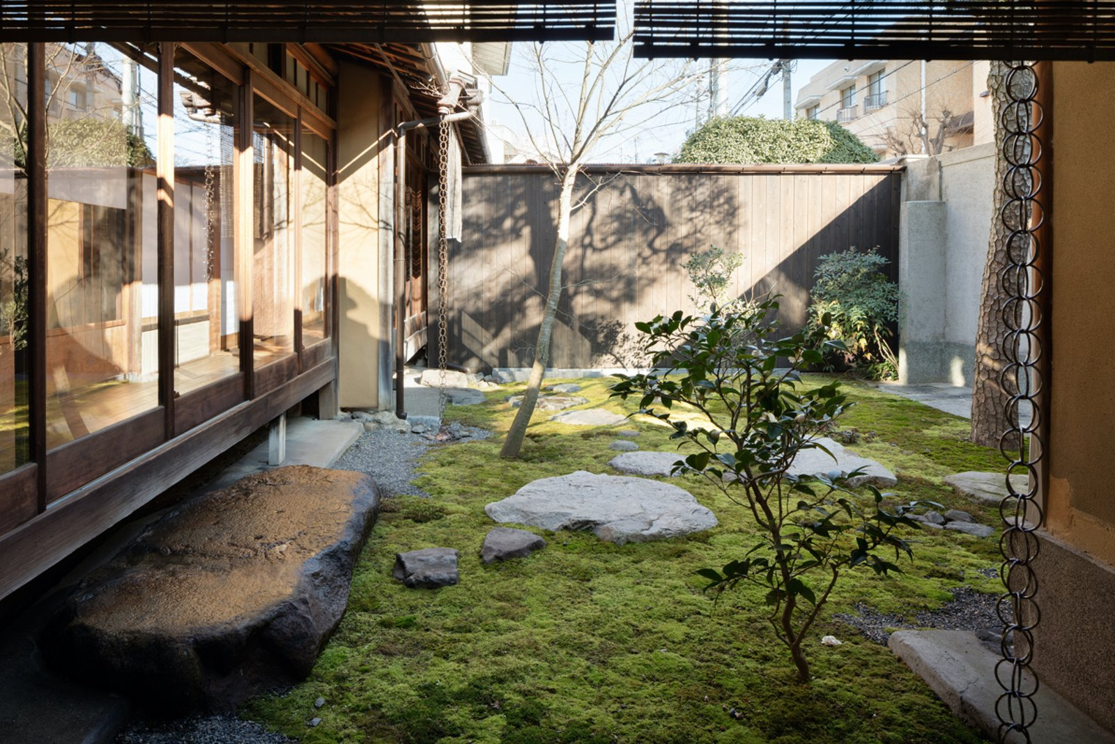 A lounge space looks onto a calming moss garden and provides the perfect zen setting to relax with a cup of tea. Tagged: Outdoor, Garden, Trees, Gardens, Grass, Boulders, and Wood Fences, Wall.  Photo 3 of 13 in A Minimalist Townhouse Provides Serene Accommodations in Historic Kyoto