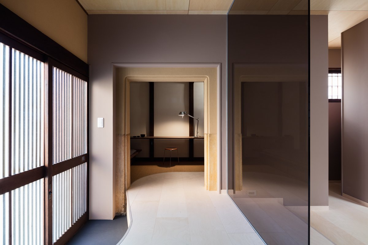Clean lines and sophisticated colors with reds, purples, and browns fill the interior.  An office space with a desk and couch is provided on the first floor. Tagged: Office, Lamps, Chair, and Desk.  Photo 6 of 13 in A Minimalist Townhouse Provides Serene Accommodations in Historic Kyoto