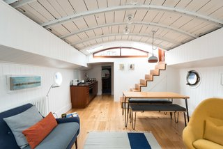 Londoners Can Live in This Scandinavian-Inspired, Converted Barge For $424K - Photo 2 of 9 - An uplifting color palette and restored midcentury furnishings, such as the 60s Greaves and Thomas Egg chair, fill the living space.